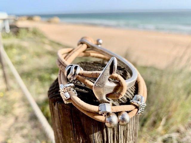 Naturfarbenes Armband mit Anker Motiv am Strand in der Sonne
