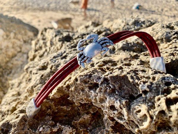 Rotes Armband mit Krebs Motiv geöffnet auf Steinen an einem Strand in der Sonne
