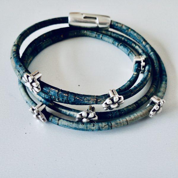 Jeansblaues Korkarmband mit silbernen Blümchen auf weißem Hintergrund