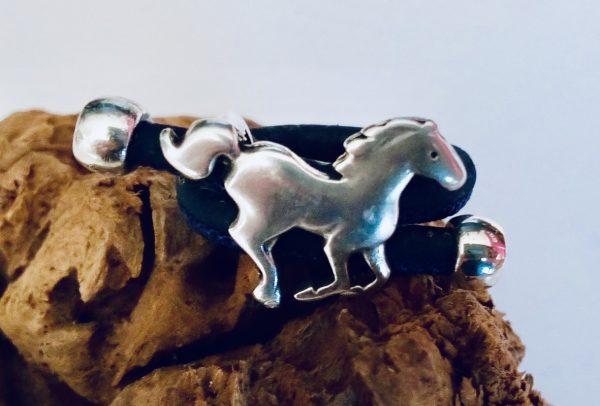 Schwarzer Korkring mit Pferd aus Silber vor hellem Hintergrund