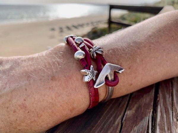 Rotes Armband mit Ankerverschluss mit sonnigem Strand im Hintergrund