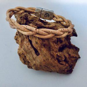 Geflochtenes Korkarmband auf einem Stück Holzen Natur Optik