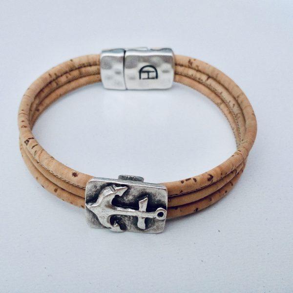 Naturfarbenes Armband mit Ankermotiv aus Silber vor einem weißen Hintergrund