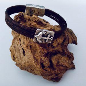 Braunes Korkarmband mit Ankermotiv aus Silber auf einem Stück Holz
