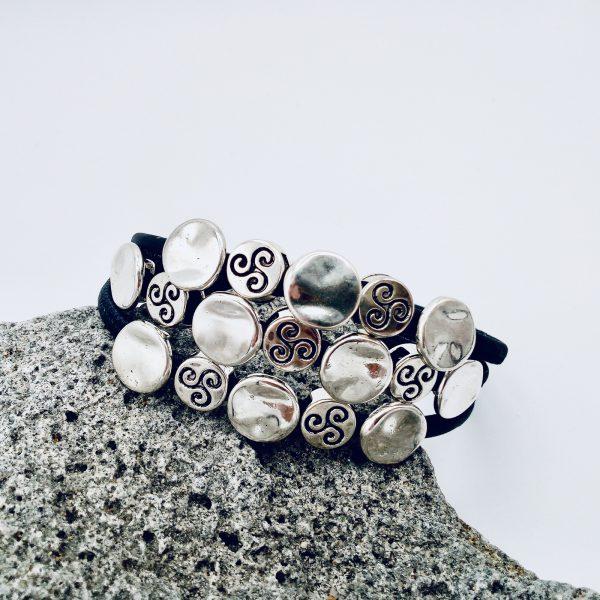 Schwarzes Silberplättchen Armband auf einem hellen Vulkanstein