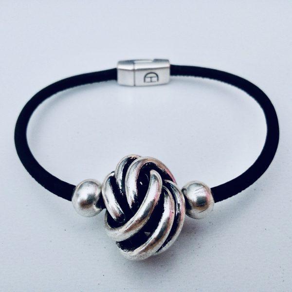 Schwarzes Armband aus Naturkork mit großer Silberkugel vor hellem Hintergrund