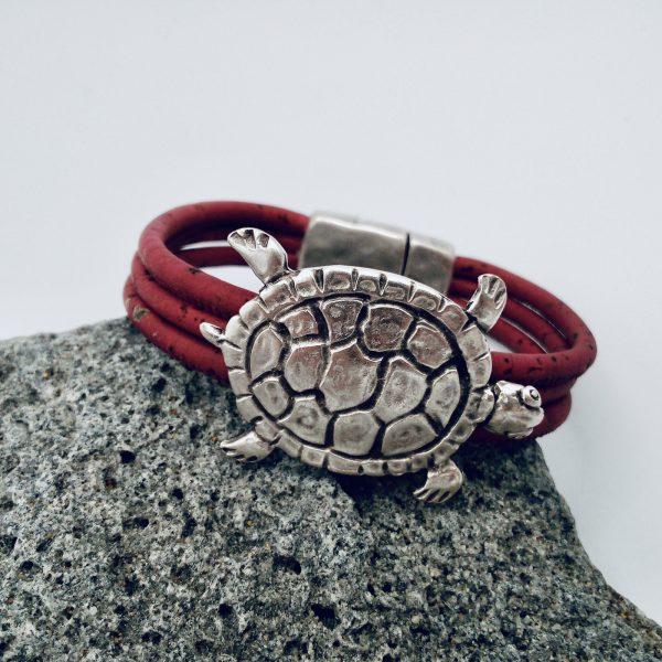 Rotes Armband mit großer Schildkröte aus Silber auf hellem Vulkanstein