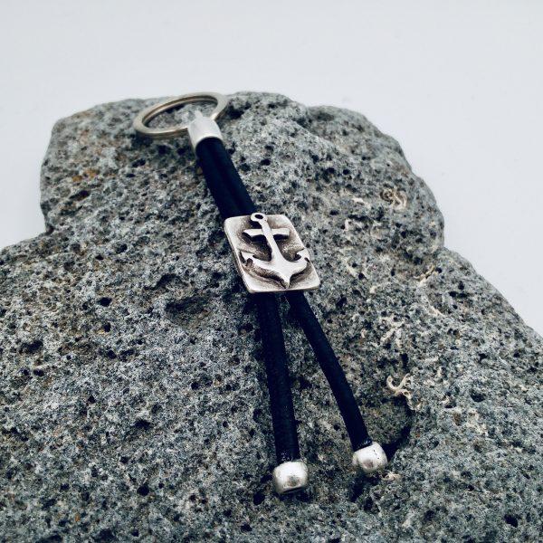 Dunkellauer Anker Schlüsselanhänger auf hellem Vulkanstein