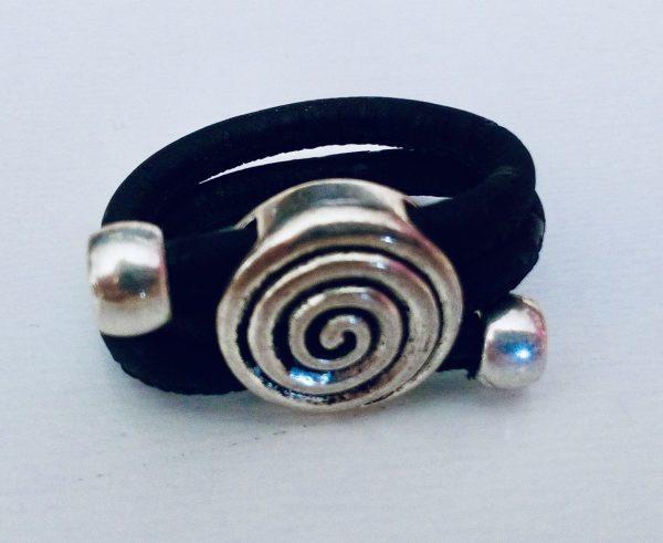 Schwarzer Korkring mit silbernem Spiralenmotiv auf hellem Hintergrund