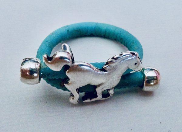 Hellblauer Korkring mit Pferd aus Silber vor hellem Hintergrund