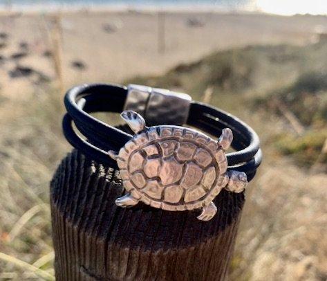 Armband mit großer Schildkröte aus Silber vor einem sonnigem Strand im Hintergrund