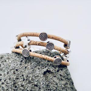 Naturfarbenes Korkarmband mit Spiral- und Seestern-Motiven aus Silber auf hellem Vulkanstein