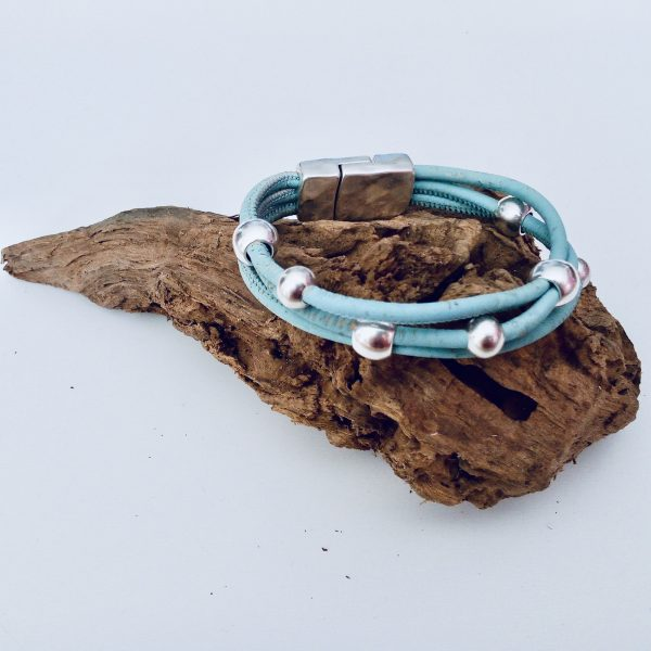 Hellblaues Korkarmband mit Silber Beads auf einem Stück Holz