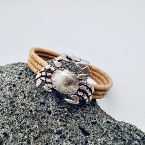 Naturfarbenes Armband mit Krebs Motiv auf grauem Vulkanstein