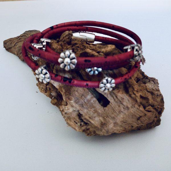Rotes Korkarmband mit silbernen Blümchen auf einem Stück Holz