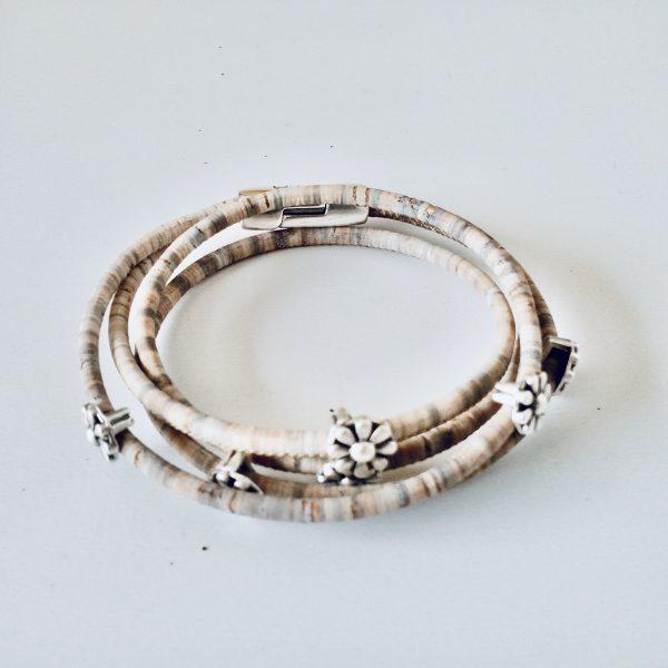 Korkarmband mit silbernen Blümchen auf weißem Hintergrund