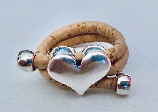 Naturfarbener Korkring mit silbernem Herz auf hellem Hintergrund