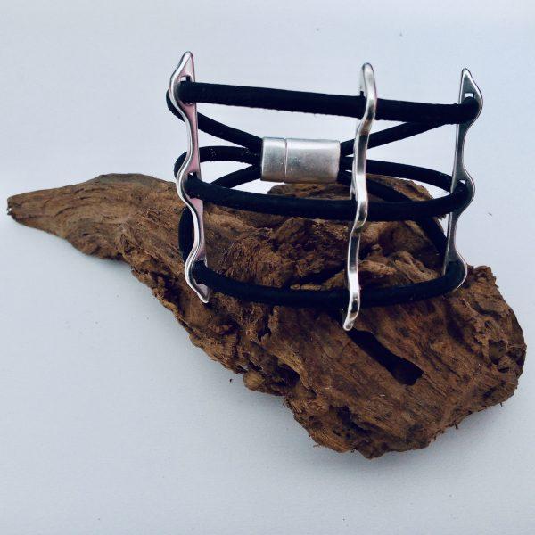 Schwarzes Korkarmband mit Silbersteg auf einem Stück Holz