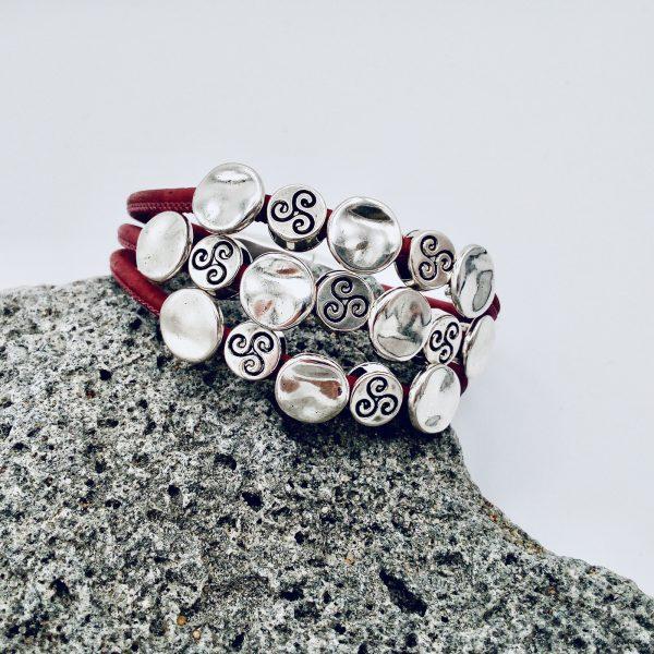 Rotes Silberplättchen Armband auf einem hellen Vulkanstein