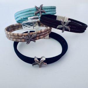 Korkarmbänder mit silbernen Seestern-Slidern in verschiedenen Farben auf weißem Hintergrund