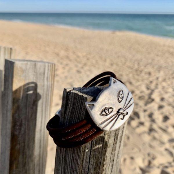Braunes Armband mit silbernem Katzengesicht auf einem Stück Holz am Strand
