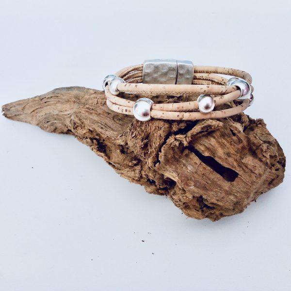 Naturfarbenes Korkarmband mit Silber Beads auf einem Stück Holz