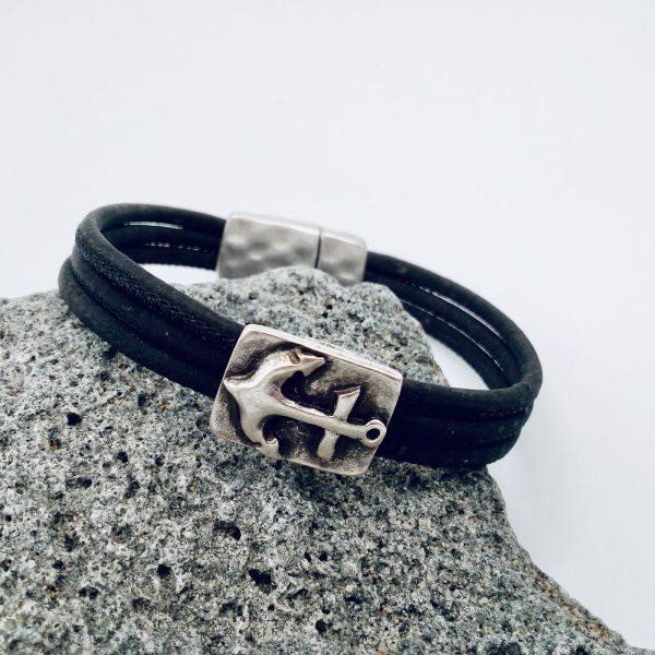 Schwarzes Anker Armband auf hellem Vullkanstein