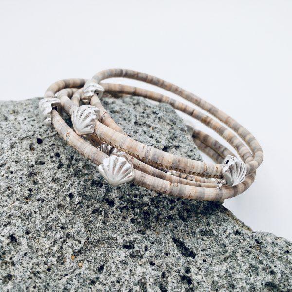 Grau-Meliertes Korkarmband mit silbernen Muscheln auf einer Skulptur aus Stein