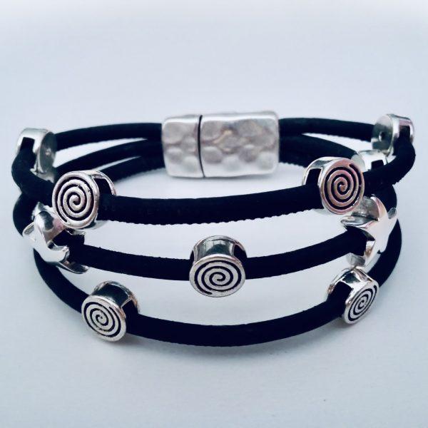 Schwarzes Korkarmband mit Spiral- und Seestern-Motiven aus Silber vor einem hellen Hintergrund