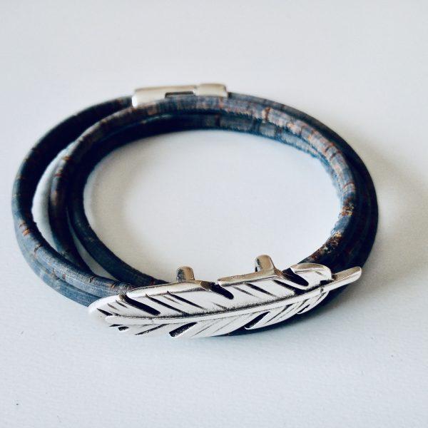 Jeansblaues Armband aus Naturkork mit zierlichem Federslider auf hellem Hintergrund