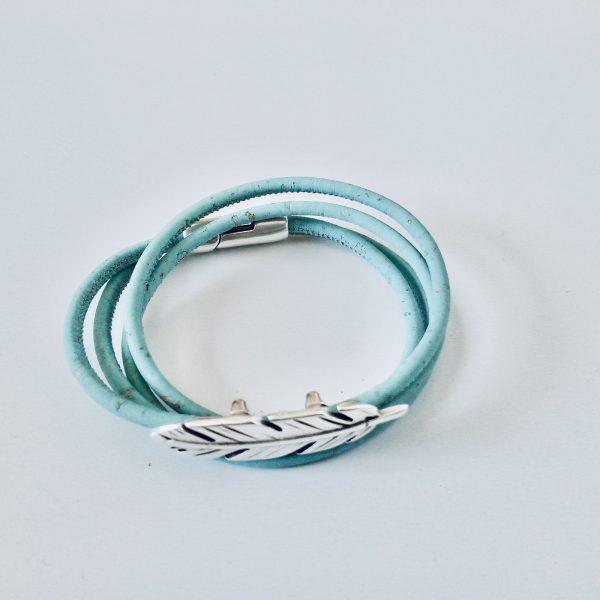 Hellblaues Armband aus Naturkork mit zierlichem Federslider auf hellem Hintergrund