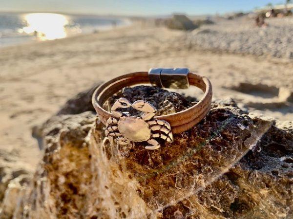 Naturfarbenes Armband mit Krebs Motiv auf Steinen an einem Strand in der Sonne