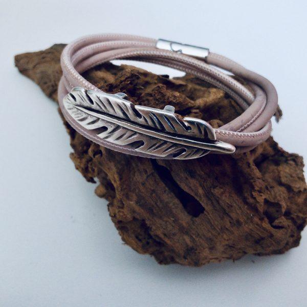 Rosafarbenes Armband aus Naturkork mit zierlichem Federslider auf hellem Hintergrund