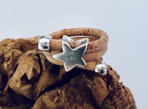 Naturfarbener Korkring mit silbernem Stern auf einem Stück Holz