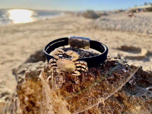 Schwarzes Armband mit Krebs Motiv auf Steinen an einem Strand in der Sonne