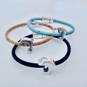 Armbänder mit silbernen Delfinmotiven in verschiedenen Farben vor einem weißen Hintergrund