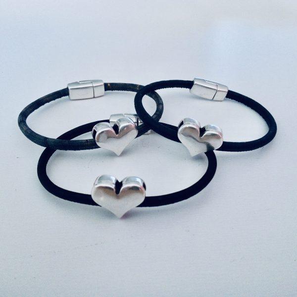Armbänder für Kinder mit silbernen Herzmotiven in verschiedenen Farben vor einem weißen Hintergrund