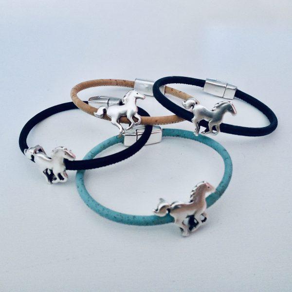 Armbänder für Kinder mit silbernen Pferdemotiven in verschiedenen Farben vor einem weißen Hintergrund