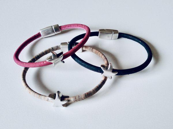 Armbänder für Kinder mit silbernen Sternmotiven in verschiedenen Farben vor einem weißen Hintergrund