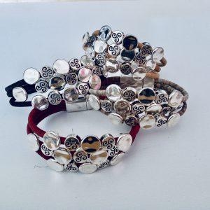 Verschiedene Silberplättchen Armbänder vor einem hellen Hintergrund