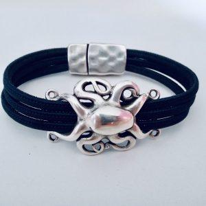 Schwarzes Korkarmband mit silbernem Oktopus auf hellem Hintergrund
