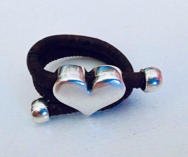 Brauner Korkring mit silbernem Herz auf hellem Hintergrund