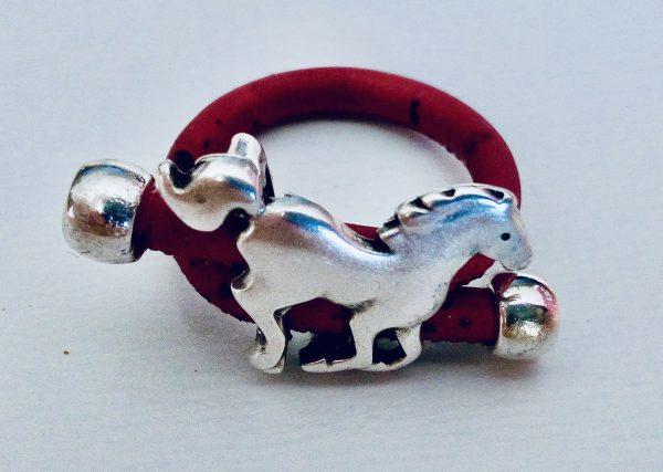 Roter Korkring mit Pferd aus Silber vor hellem Hintergrund