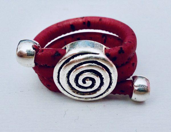 Roter Korkring mit silbernem Spiralenmotiv auf hellem Hintergrund
