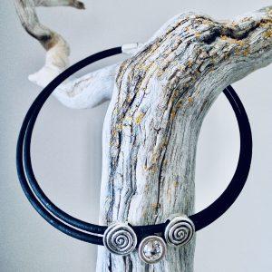Schwarze Spiralen Korkkette mit transparentem Swarovski Stein über einen Ast gelegt auf hellem Hintergrund