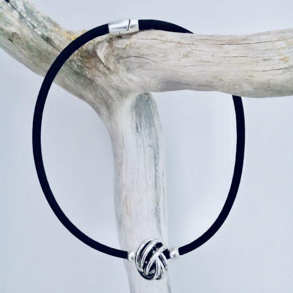 Schwarze Korkkette mit großer Silberkugel über einen Ast gelegt vor einem hellen Hintergrund
