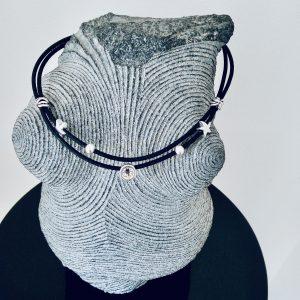 Schwarze Korkkette mit silbernen Seesternen und transparentem Swarovski Stein auf einer Skulptur aus Stein