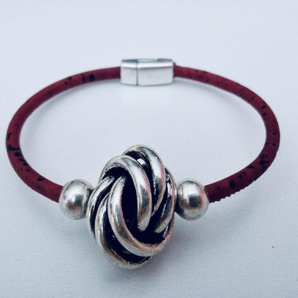 Rotes Armband aus Naturkork mit großer Silberkugel vor hellem Hintergrund