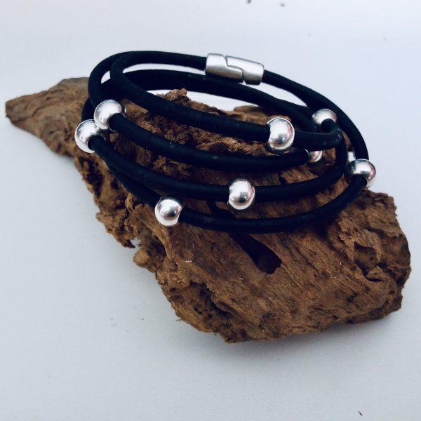 Schwarzes Armband aus Naturkork auf einem Stück Holz