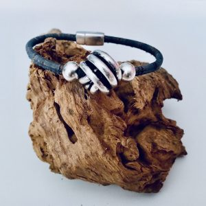 Jeansblaues Armband aus Naturkork mit großer Silberkugel auf einem Stück Holz
